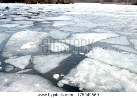 Rural landscape with melt broken ice floes floating on the river on a spring day