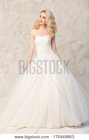 Portrait of the gorgeous smiling blonde bride with beautiful curly hair in a white wedding dress to the full-length on a light background. beautiful young model with bridal hairstyle and makeup in a white magnificent dress.
