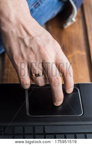 Close-up shot of men's hand touching trackpad on laptop. Empty space on keys. Wooden backdround