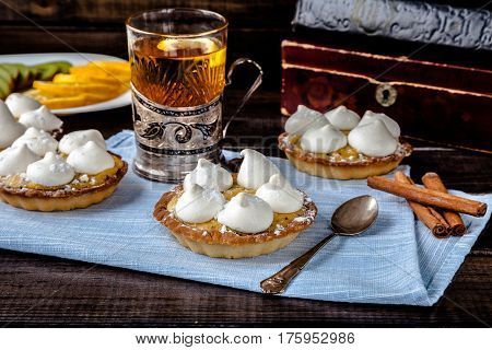 Delicious homemade mini tarts (tartlets) with fruit kiwi and lemon kurd cream with meringue on retro background. Served with clear tea mug in cup holder and fruits slices. Tasty sweet small dessert.