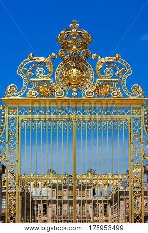 Golden ornate gates of the Palace of Versailles (Chateau de Versailles) over blue sky. Paris France