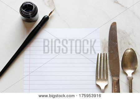 Pen, ink, lined paper and vintage silverware with room for copy