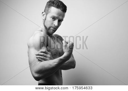 Handsome man with shoulder ache at the white background. Black and white.