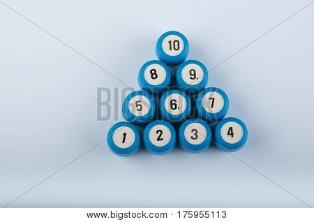 Triangle made of blue plastic lotto kegs with different numbers lay on white background