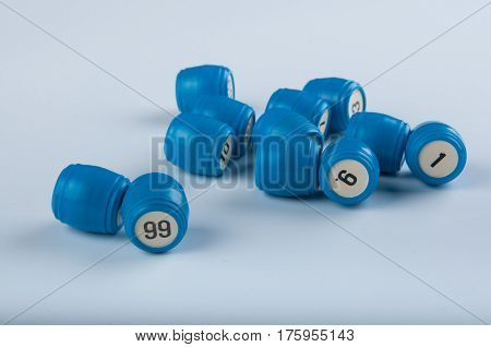 Blue plastic kegs for lotto game with numbers lay on white background. Numbers ninety nine nine one