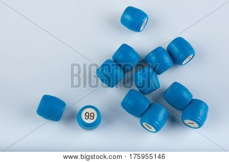 Pile of plastic lotto kegs with numbers lay on white background. View on number ninety nine