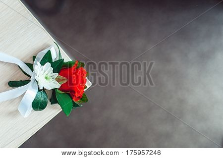 little luxury wedding boutonniere with roses with white ribbon on the corner of the table. Gray background