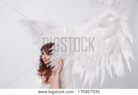 beautiful young model with open angel wings on white background
