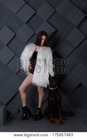 Young sexy brunette in undewear with white fur with angry doberman dog looking at the camera