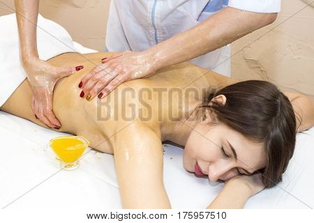 Girl treatment massage honey body wrap in a beauty salon