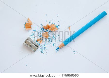 blue wooden pencil sharpener and blue pencil shavings on white