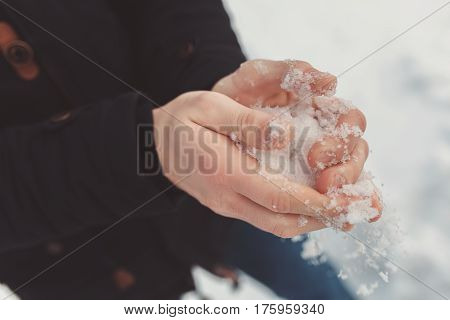 Male hands close-up. A man in a warm jacket holds snow in his frozen hands