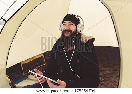 beardie in winter warm clothes with white tablet in hands listening music on headphones while sitting in a tent. concept of advanced teenager in technology world