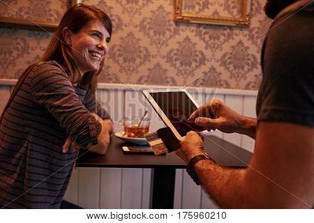 Laughing Young Woman Paying At A Bar