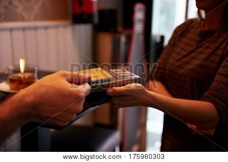 Credit Card Held Above Card Machine