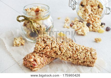 Two muesli bars with fruit crunchy scattered on a paper and linen background healthy food concept