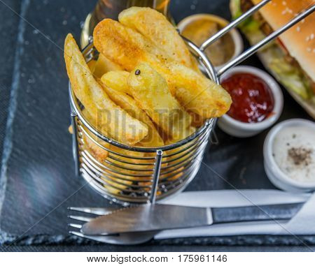Chips In A Metal Basket, A Background Crusty White Bread With Sesame Seeds,  Three Sauces, Chips In