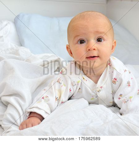 a beautiful smiling baby in the bed