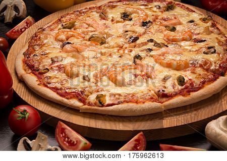 Pizza with seafood, mozzarella, mussels, octopus, squid, salmon, shrimp on an isolated black background