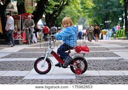 Child with a bike cycling in a park Sofia Bulgaria