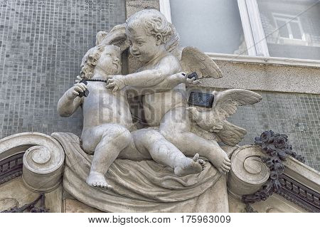 Stone statue baby angel plays with a young child