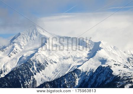 Mountain piek with clouds and snow in Austian Alps
