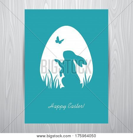 Easter greeting card design with standing rabbit silhouette in an egg shaped white frame. Placed on a grey wooden background