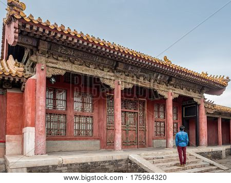 Beijing, China - Oct 30, 2016: Man admiring the complex architectural design of an old palace residential outhouse inside Forbidden City (Gu Gong, Palace Museum).