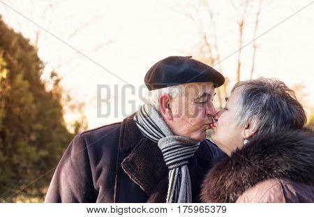 Happy senior couple kissing outdoor, affectionate, togetherness