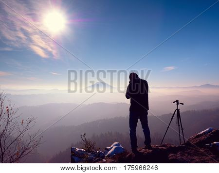 Photographer Stay With Camera Ind Hands  At Tripod On Rock