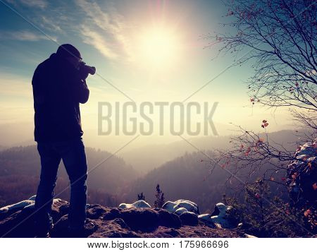 Tall  Man Is Taking Photo By Mirror Camera On Neck. Snowy Rock
