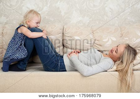 Little girl is hugging mom's knees, she is laying on the sofa and smiling