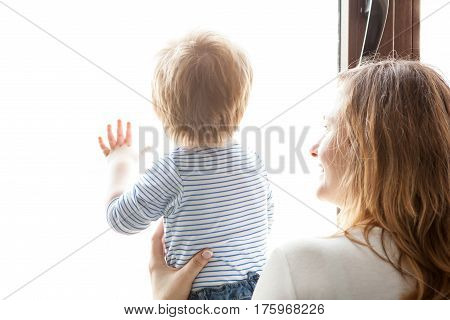 Mother And Son Looking Together Through The Window