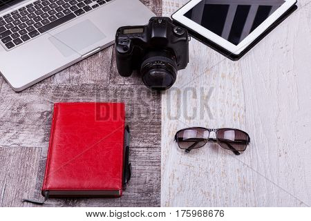 Over Top Photo Of Camera, Laptop, Writing Notebook And Sunglasses