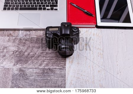 Over top photo of camera and laptop on wooden background