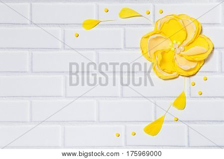 White Horizontal Background With Handmade Gentle Yellow Flower and Feathers, Lying Flat on the White Brick Wall .Top View. Have an Empty Place For Your Text.