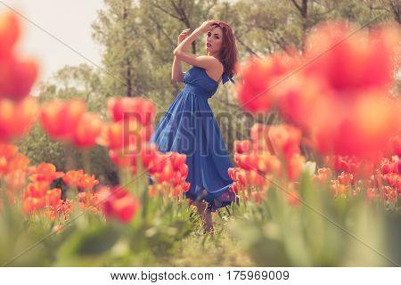 Beautiful Woman In Red Tulip Flowers Field