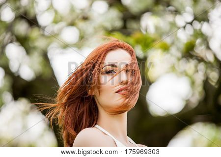Romantic redhead woman outdoor photo in summer on blurred tree flower background