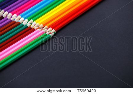 Colored pencils lie opposite on the dark background. Tips of the pencils. Place for the text. Concept. Art and design. Drawing and painting.