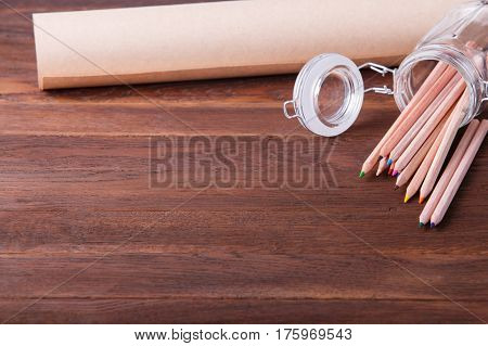 School supplies on a wooden surface. colored pencils in a glass and roll of paper on a wooden table. Brown background. Concept. Education and school. Drawing nad painting. Art and design.