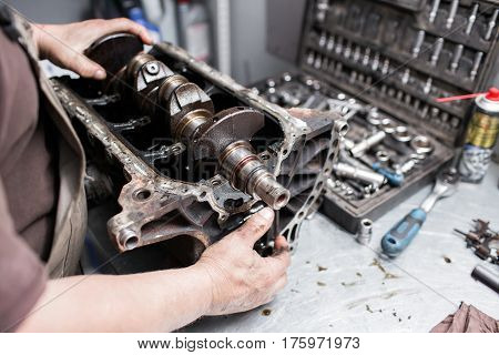 Engine crankshaft, valve cover, pistons. mechanic repairman at automobile car engine maintenance repair work.