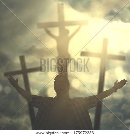 Portrait of Asian male is raising hands while praying to God with three crucifixes under sunbeam