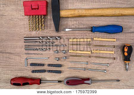 Screw With Dowel, Screwdriver, Hammer On Desk.