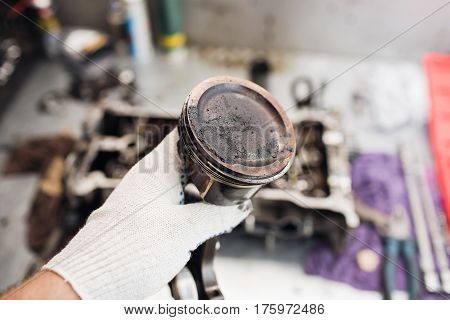 Car mechanic in garage with old car engine piston