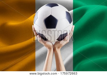 Soccer ball on the top of arms with national flag background of Ivory Coast