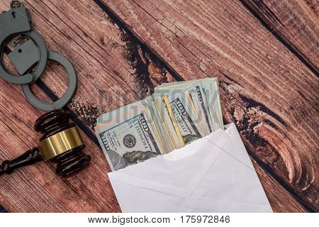 Dollar In Envelope With Handcuff, Wooden Hammer.