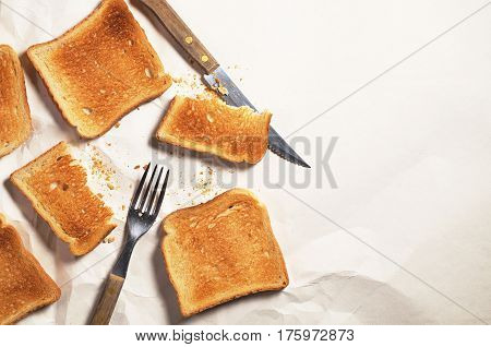 Slice of toasted bread fork and knife on crumpled paper background top view. Space for text