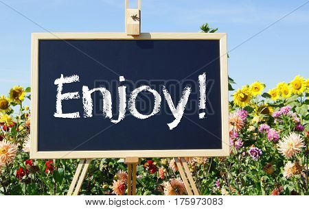 Enjoy! Easel with text in the summer garden with flowers
