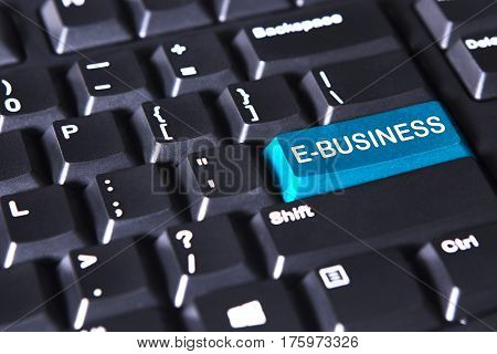 Closeup of modern keyboard with e-business text on the blue button