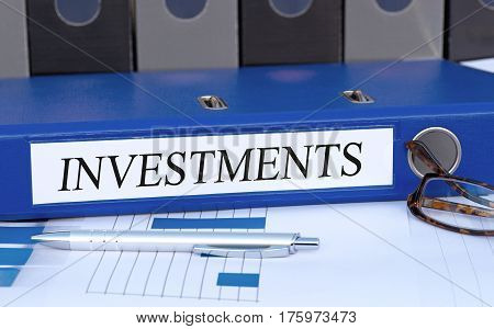 Investments - blue binder on desk in the office